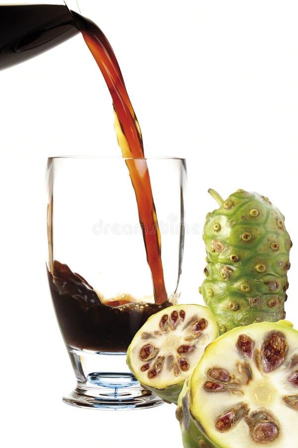 Fruktsaft från Noni frukt som flödar in i coctailexponeringsglas royaltyfri fotografi