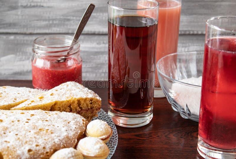 Fruktsaft i ett exponeringsglas i bakgrunden, en paj på en bunke och driftstopp i en liten krus royaltyfria foton