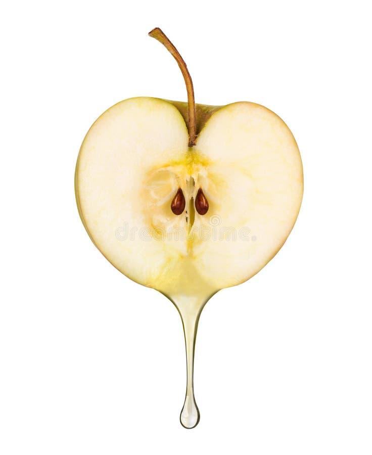 Fruktsaft i form av droppe som flödar från det nya äpplet på vit arkivfoton
