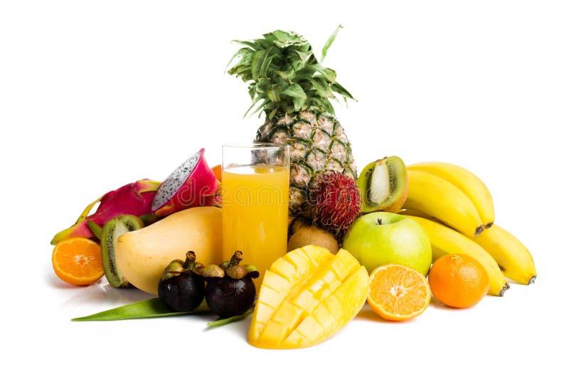 Fruktsaft i glass och tropisk frukt arkivbilder