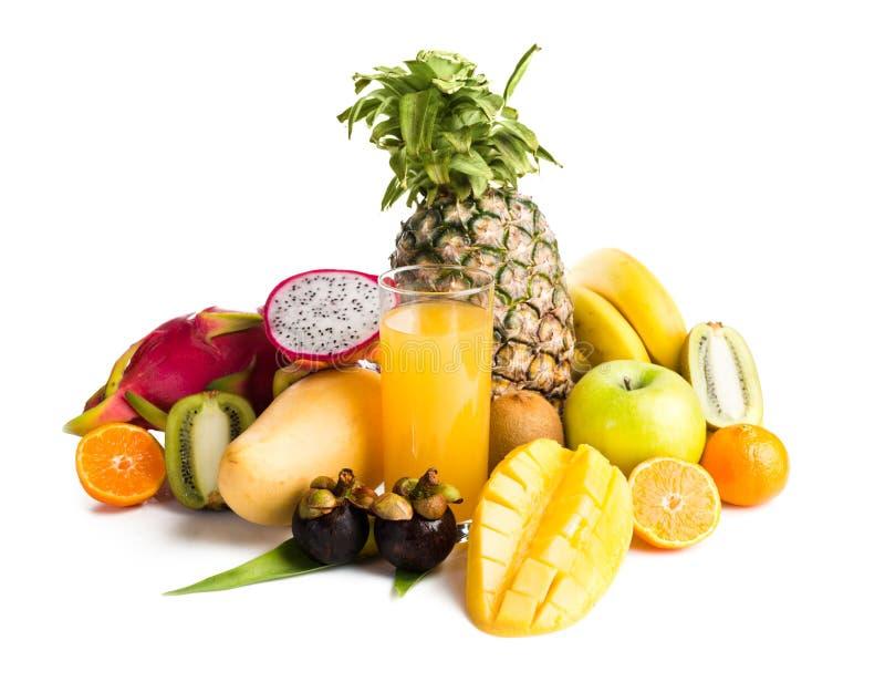 Fruktsaft i glass och tropisk frukt fotografering för bildbyråer