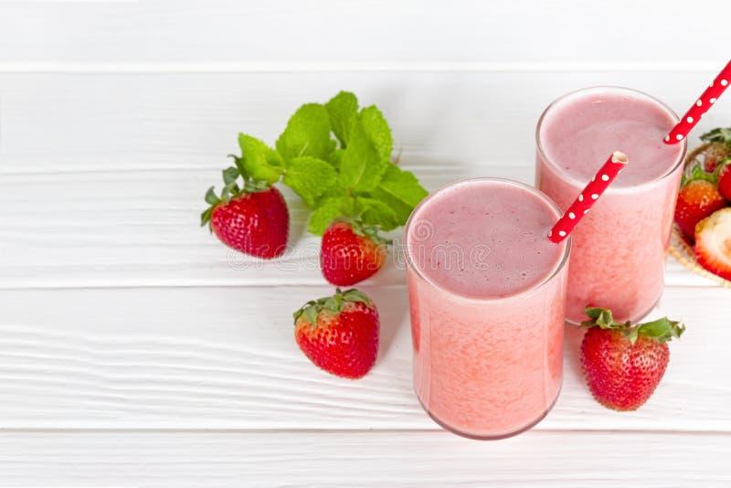 Fruktsaft och jordgubben för jordgubbesmoothiesyoghurt bär frukt för frukost i morgonen på vit wood bakgrund royaltyfri bild