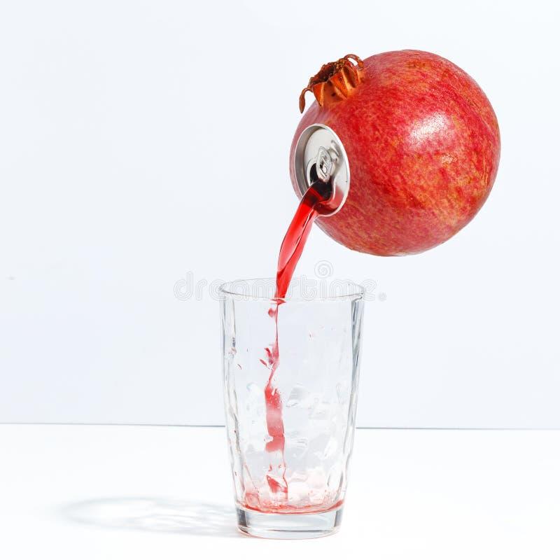 Fruktsaft som flödar från en mogen granatäpple in i ett exponeringsglas Idérikt begrepp av ny fruktsaft arkivbild