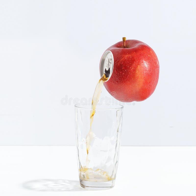 Fruktsaft som flödar från ett moget äpple in i ett exponeringsglas Idérikt begrepp av ny fruktsaft arkivfoto