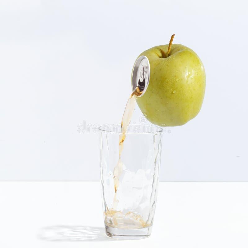 Fruktsaft som flödar från ett moget äpple in i ett exponeringsglas Idérikt begrepp av ny fruktsaft royaltyfria bilder
