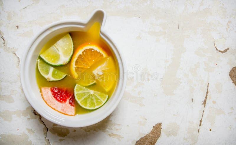 Fruktsaften från citrusfrukter - grapefrukt, apelsin, tangerin, citron, limefrukt i en kopp arkivbilder