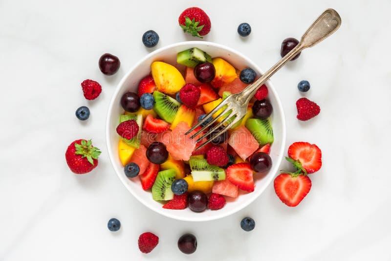 Fruktsallad med vattenmelon, jordgubben, körsbäret, blåbäret, kiwin, hallonet och persikor med gaffeln i en bunke arkivfoto