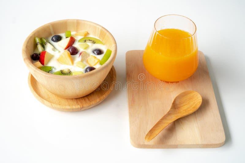 Fruktsallad med yoghurt på en träbunke och en orange fruktsaft royaltyfri bild