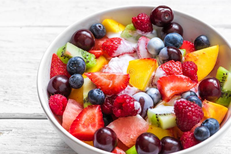 Fruktsallad med yoghurt, vattenmelon, jordgubben, k?rsb?ret, bl?b?ret, kiwin, hallonet och persikor i en bunke sund mat royaltyfri fotografi