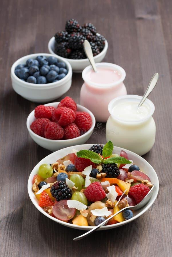 Fruktsallad, nya bär och yoghurter på en trätabell royaltyfri foto