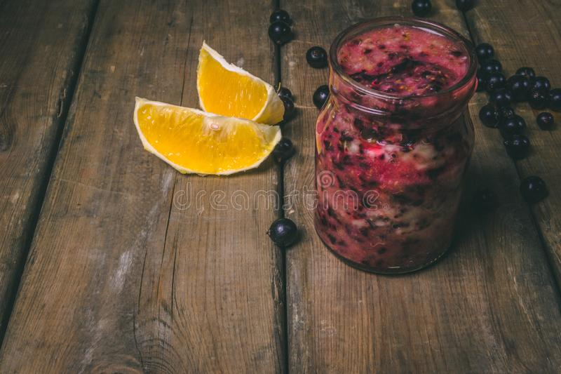 Fruktsmoothies gjorde med nya ingredienser på en träbakgrund Svart vinbär, apelsin sund begreppsmat royaltyfri foto
