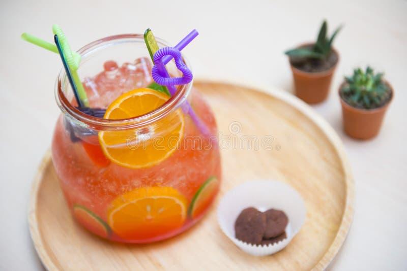Fruktstansmaskin med den skivad apelsinen och limefrukt i den stora bunken för drink royaltyfri bild