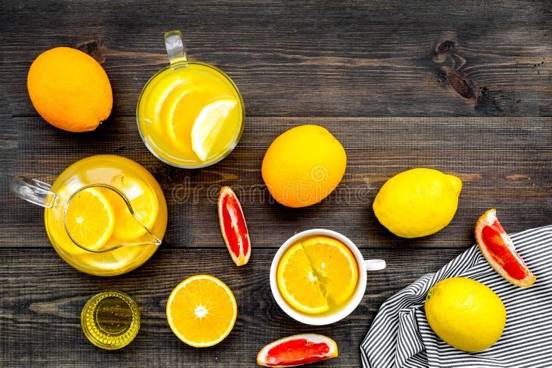 Fruktte Tekopp och tekanna bland citrus på mörkt träutrymme för kopia för bästa sikt för bakgrund royaltyfri fotografi