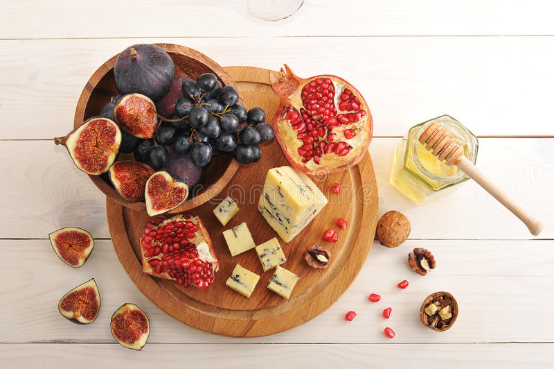Fruktuppläggningsfat - fikonträd, druvor, granatäpple och ost med honung arkivbilder