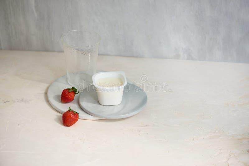 Fruktyoghurt i plast- beh?llare med en jordgubbe p? vit bakgrund arkivbild
