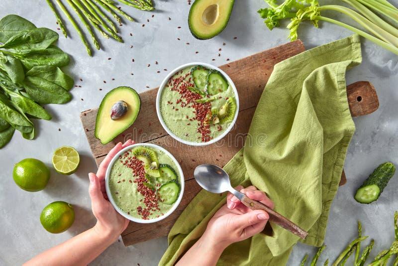 Frullati appeni preparato dall'avocado, dall'asparago, dal cetriolo e dal kiwi con lino su un tavolo da cucina grigio Alimento de fotografia stock