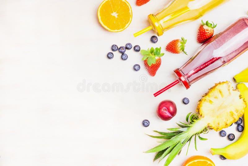 Frullati rossi e gialli in bottiglie con gli ingredienti di frutti su fondo di legno bianco, vista superiore, posto per testo immagini stock