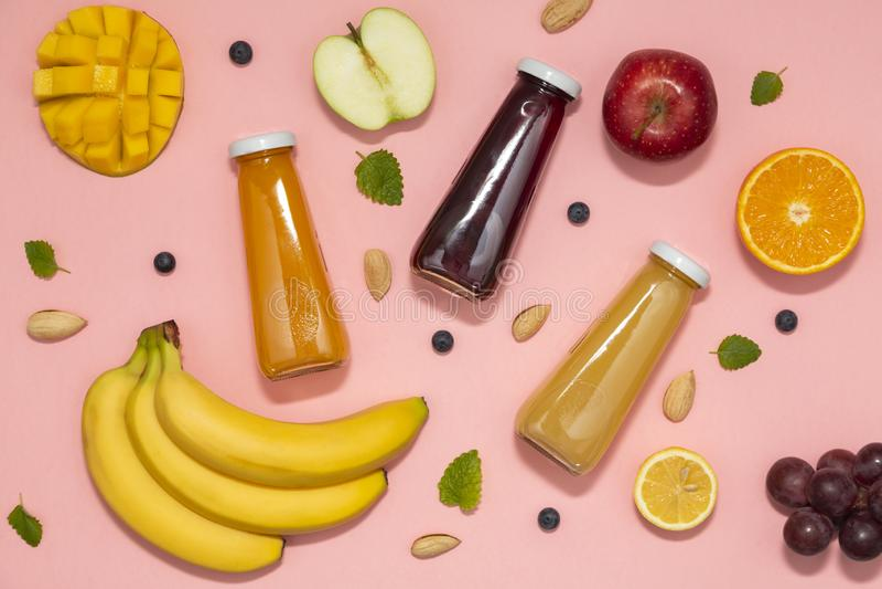 Frullati variopinti in bottiglie con la frutta fresca su fondo rosa Disposizione piana, vista superiore immagini stock libere da diritti