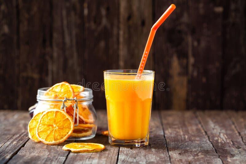 Frullato arancio servito sulla tavola decorata con le fette di frutta arancio fotografie stock libere da diritti