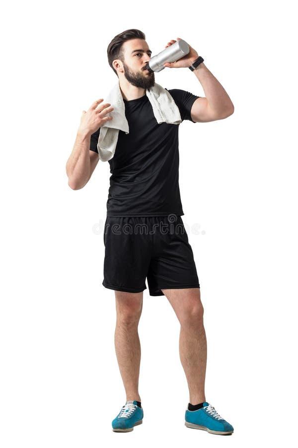 Frullato bevente del giovane atleta dal recipiente di plastica con l'asciugamano intorno al collo immagine stock