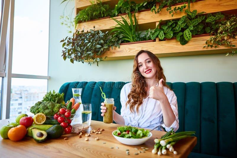Frullato bevente della giovane donna nel bello interno con i fiori verdi sui precedenti e la frutta e le verdure fresche sopra fotografia stock libera da diritti