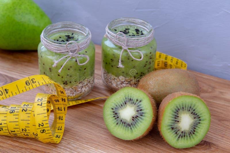 Frullato del kiwi con cereale su una tavola di legno fotografia stock libera da diritti