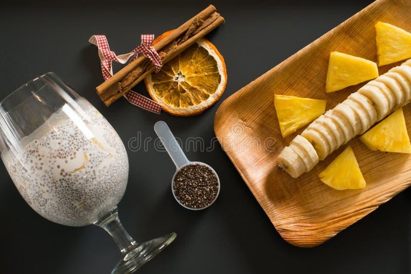 Frullato del mango con la banana, i semi di chia ed il latte di cocco su fondo scuro fotografie stock libere da diritti