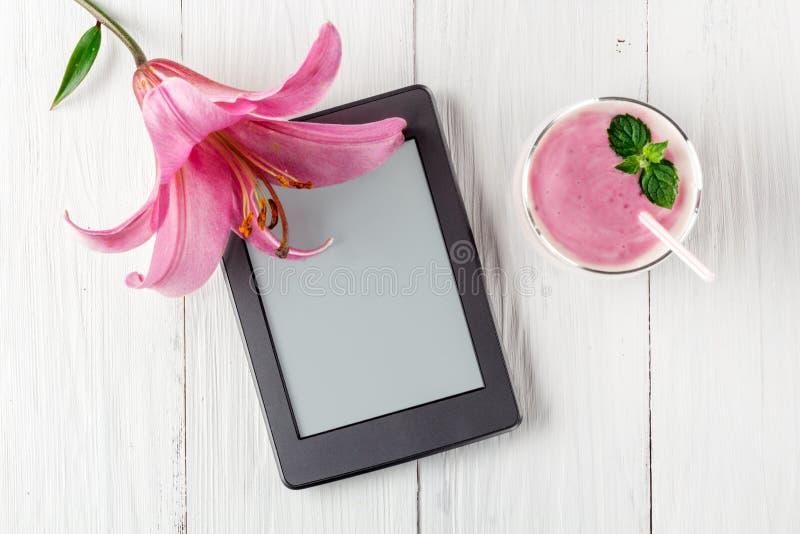 Frullato della bacca con yogurt ed il libro elettronico fotografia stock