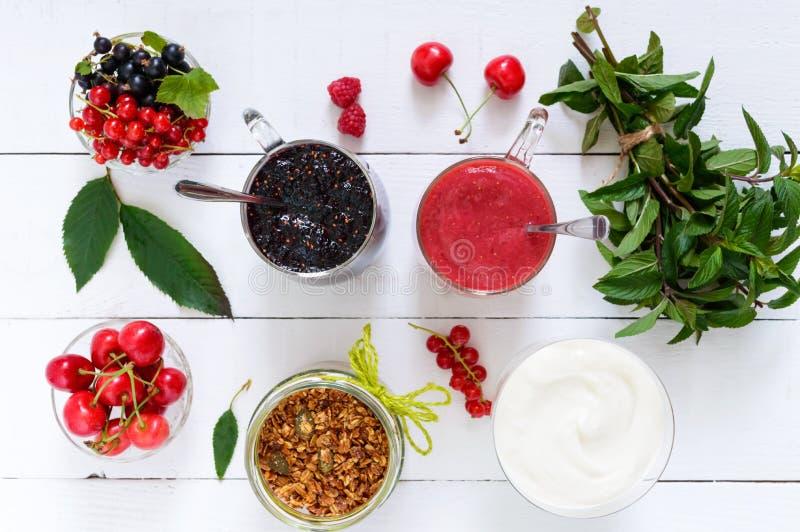 Frullato della bacca dentro delle tazze di vetro, yogurt, granola, bacche fresche sulla tavola di legno bianca Vista superiore Nu fotografia stock libera da diritti