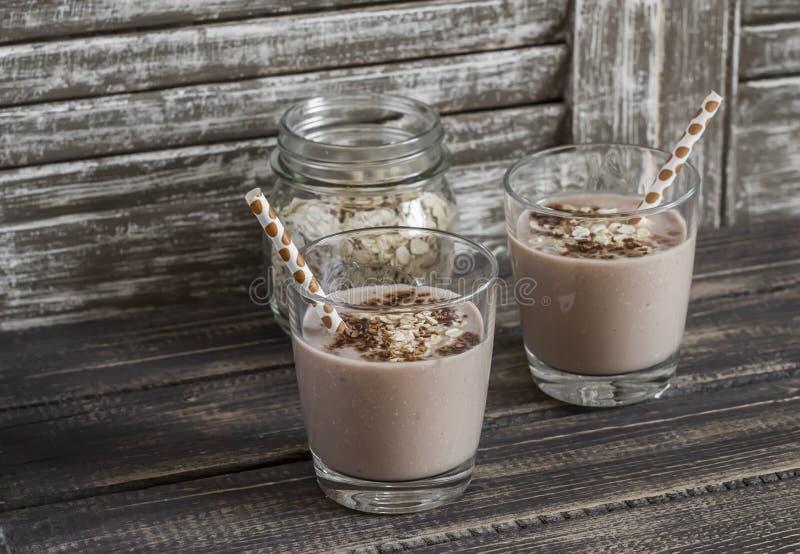 Frullato della banana, della farina d'avena e del cioccolato Su un fondo di legno rustico scuro Bevanda sana immagini stock