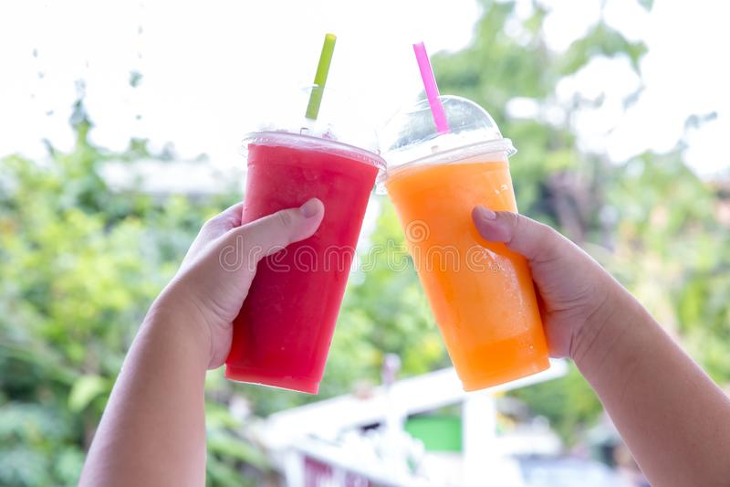 Frullato della frutta Mano che tiene tazza di plastica del frullato colourful della frutta al caff? sveglio Mano che tiene tazza  immagine stock libera da diritti
