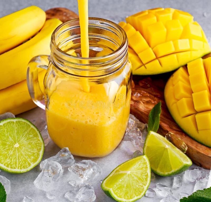 Frullato giallo sano del mango della banana con le fette di calce, di menta e di ghiaccio fotografie stock libere da diritti
