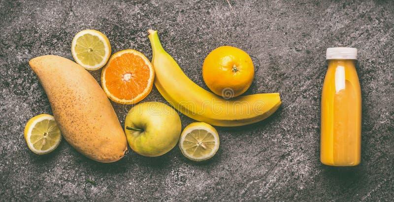 Frullato organico giallo di frutti con il limone, le arance, la mela, il mango e la banana in bottiglia sulla tavola grigia del g immagini stock