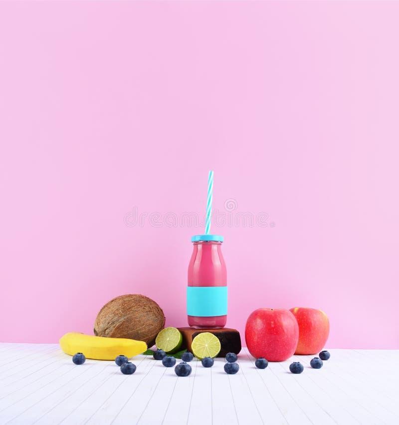 Frullato rosa con i frutti tropicali sulla tavola bianca fotografia stock