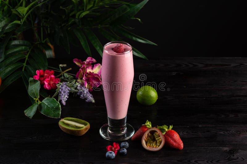 Frullato rosa in un vetro alto e frutti su un fondo scuro immagine stock