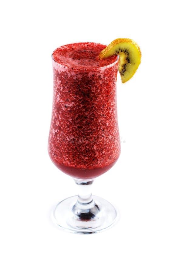 Frullato rosso del latte e della frutta in un vetro sulla gamba decorata con il kiwi su un fondo bianco isolato immagini stock