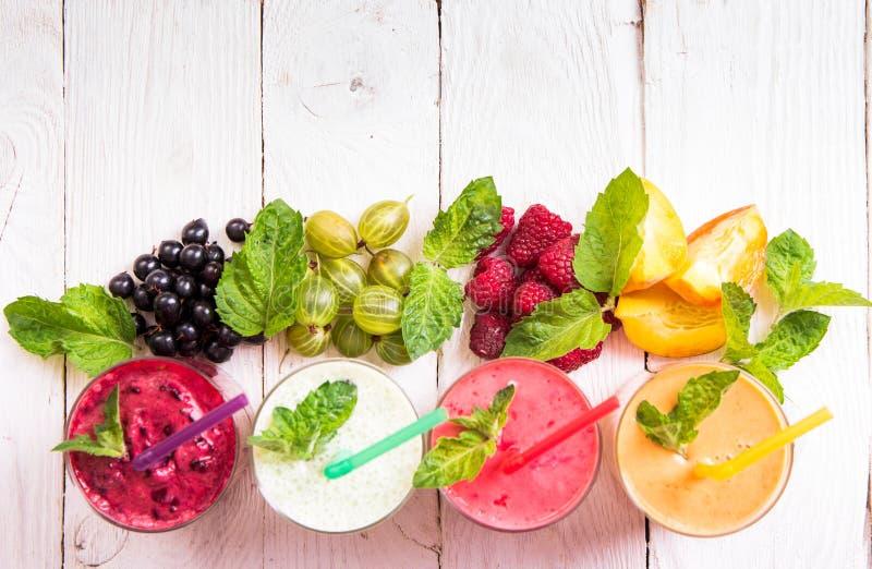 Frullato in un vetro e una frutta fresca e le bacche fotografie stock