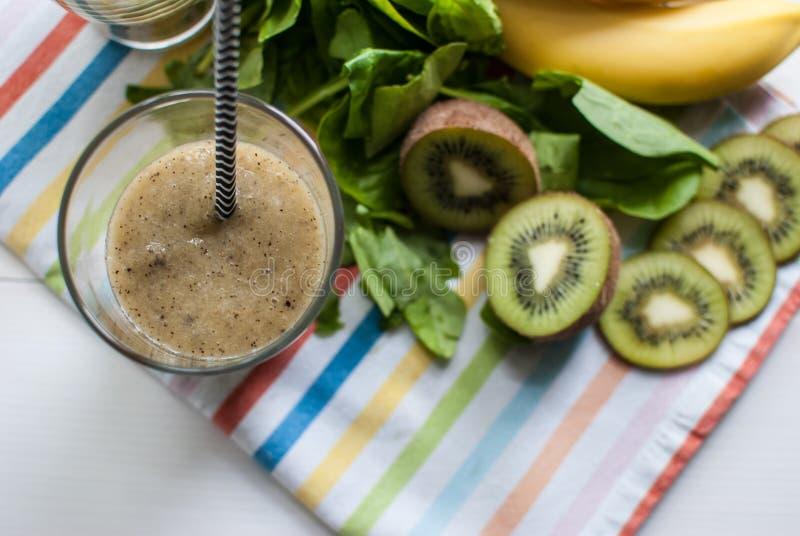 Frullato verde con il kiwi, la banana e gli spinaci fotografia stock