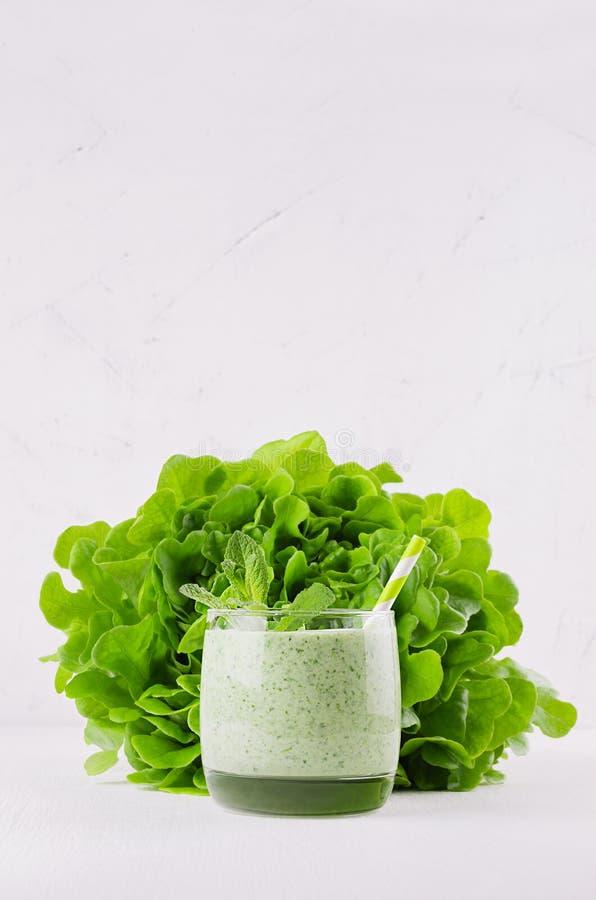 Frullato verde di recente mescolato degli spinaci in vetro con paglia, foglie di menta, insalata del covone immagine stock
