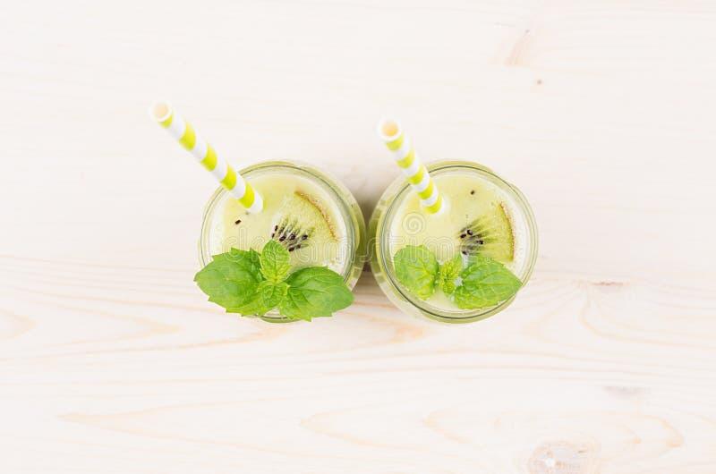 Frullato verde di recente mescolato del kiwi in barattoli di vetro con paglia, foglia della menta, vista superiore immagini stock