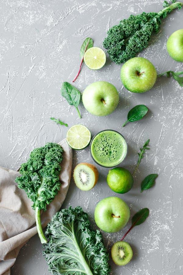 Frullato verde sano con i frutti, il cavolo e gli spinaci verdi freschi su fondo grigio, vista superiore fotografie stock