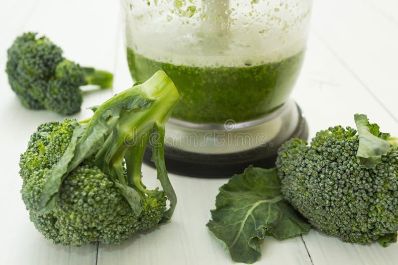 Frullato verde in un miscelatore e nei broccoli crudi su fondo di legno fotografia stock libera da diritti