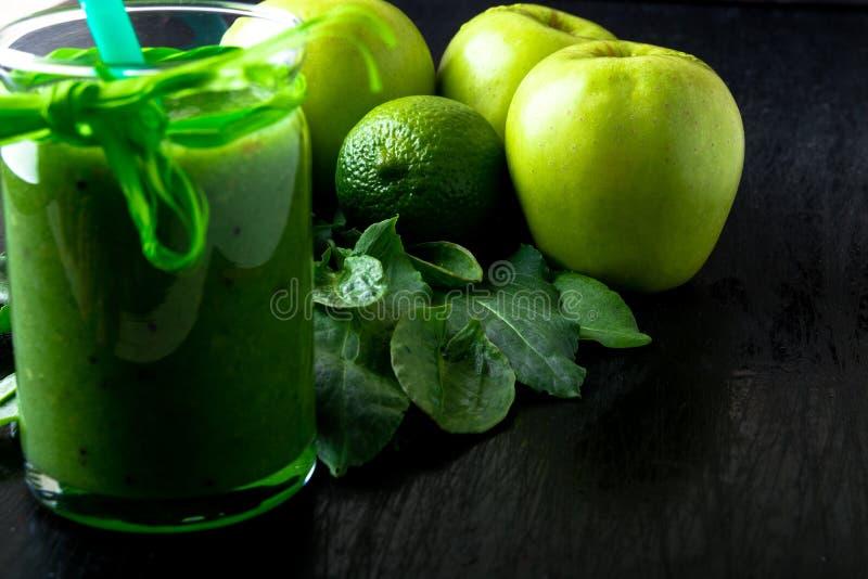 Frullato verde vicino agli ingredienti per su fondo di legno nero Apple, calce, spinaci detox Bevanda sana Alimento puro immagine stock