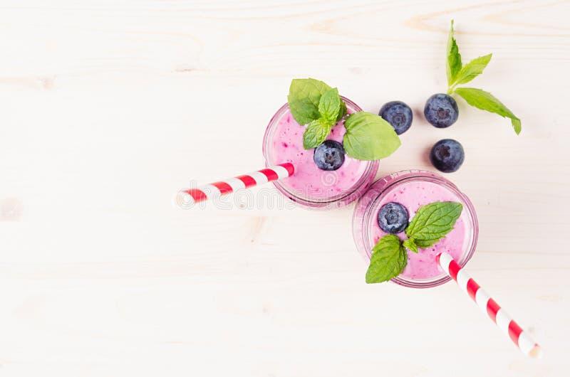 Frullato viola di recente mescolato della frutta del mirtillo in barattoli di vetro con paglia, foglie di menta, bacche, vista su immagini stock