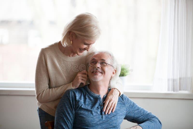 Frun lutade över till hennes make som bakifrån kramar honom royaltyfri fotografi