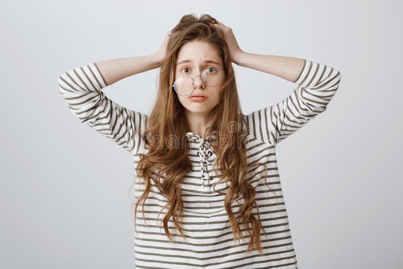 Frustração do sentimento da menina da incapacidade fixar o problema Retrato da jovem mulher preocupada e forçada que guarda as mã imagem de stock