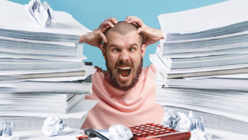 Frustrated abrumó el ejecutivo que trabajaba en la oficina y sobrecargado con papeleo fotografía de archivo