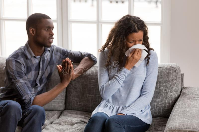 Frustrated African American man apologizing to woman after quarr. Frustrated African American men apologizing to women after quarrel, crying wife with royalty free stock images