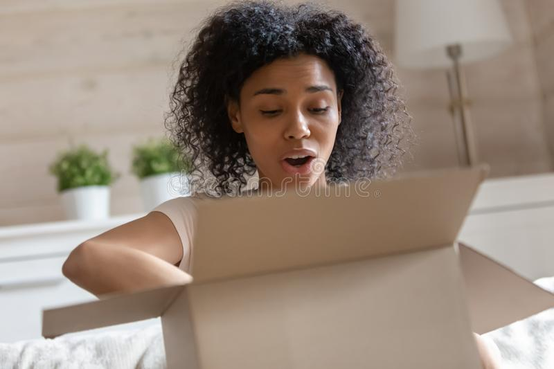 Frustrated african American woman disappointed with delivery service. Frustrated african American millennial woman open cardboard box feel disappointed by wrong royalty free stock photo
