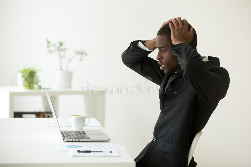 Frustrated African American reading company bankruptcy news. Shocked overwhelmed frustrated African American manager looking at laptop in despair, reading bad stock image